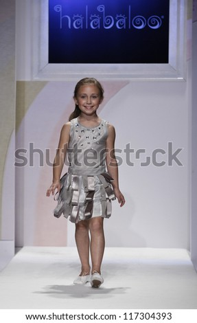 NEW YORK - OCTOBER 21: Girl walks runway for petite Parade show by Halabaloo during kids fashion week sponsored by Vogue Bambini & Swarovski Elements at Industria Superstudio on October 21 2012 in NYC