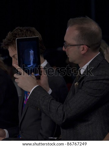 NEW YORK - OCTOBER 16: Michael Landry of randyfenoli uses iPad to snap shot of model on runway for Badgley Mischka collection at New York International Bridal Week at 94 Pier on Oct 16 2011 in NYC