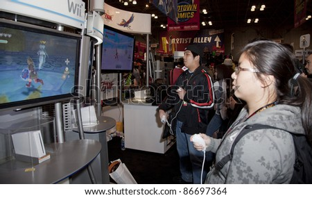 NEW YORK - OCTOBER 15: Unidentified participants try new games for Wii console New York Comic Con 2011 in Javits Center on October 15, 2011 in New York.