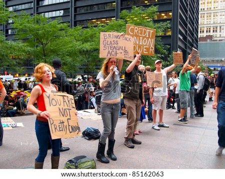 NEW YORK - SEPT. 21: A group of young people hold signs and shout messages at the Occupy Wall Street demonstration  near the New York Stock Exchange on September 21, 2011 in New York City.