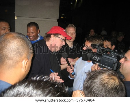 NEW YORK - SEPT 22: Director Michael Moore (C) speaks to reporters near the NY Stock Exchange on September 22, 2009 in New York City