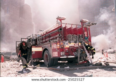 NEW YORK - SEPTEMBER 11:  A New York City firefighter carries a fire hose as he works near the area known as Ground Zero after the collapse of the Twin Towers September 11, 2001 in New York City.