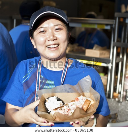 NEW YORK - SEPTEMBER 01: A server prepares to serve a dish at the Fulton Seafood food court area at US Open at USTA Billie Jean King National Tennis Center on September 01, 2011 in New York City.