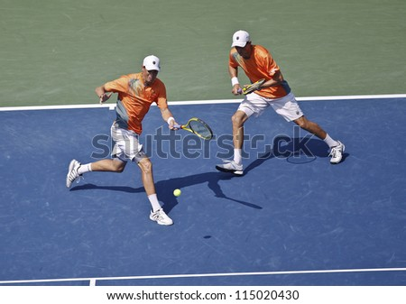 NEW YORK - SEPTEMBER 07: Bob & Mike Bryan of USA play ball during men double final against Leander Paes of India & Radek Stepanek of Czech Republic at US Open tennis tournament on Sep 7, 2012 in NYC - stock photo
