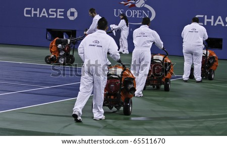 NEW YORK - SEPTEMBER 13: Crew members clean the court after the rain during final match of US Open Tennis Championship between Rafael Nadal of Spain and Novak Djokovic of Serbia on Sep 13, 2010 in NYC