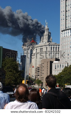 NEW YORK - SEPTEMBER 11 - Crowd witnesses South Tower of the World Trade Center collapsing as a result of terrorist attack while North Tower burns on September 11, 2001 at 9:59 am in New York.