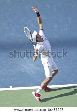 NEW YORK - SEPTEMBER 10: Novak Djokovic of Serbia returns during semifinal match against Roger Federer of Switzerland at USTA Billie Jean King National Tennis Center on September 10, 2011 in New York City