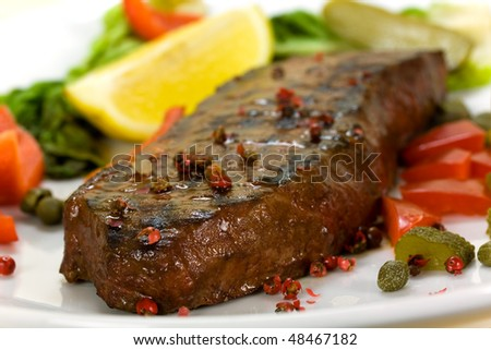 New York Steak- meat on Green Salad,Red Bell Pepper and Capers over plate