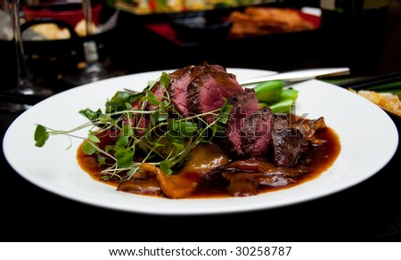 New York strip steak thinly sliced.  Medium-rare, with micro-greens in a cognac sauce.