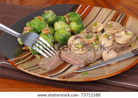 New York strip steak topped with mushrooms and brussels sprouts