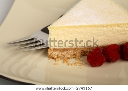 New York style cheesecake on a plate with raspberries