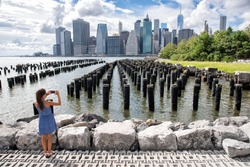 New York tourist woman taking mobile picture with smartphone. Manhattan city skyline waterfront lifestyle. People walking enjoying view of downtown from the Brooklyn bridge park Pier 1 salt marsh.