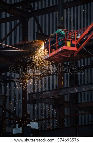 NEW YORK, USA - Apr 30, 2016: Workers on the construction site. Metal welding work at the construction site in Lower Manhattan. Sparks from welding work #574693576
