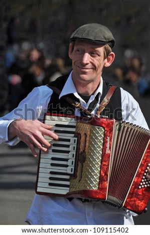 NEW YORK, USA - APRIL 9: A Busker plays a beautiful red Weltmeist Piano Accordion in the streets of Greenwich Village on April 09, 2008 in New York.