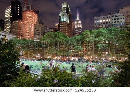 NEW YORK,USA - AUGUST 17,2016 : Bryant Park in New York City illuminated at night and surrounded by skyscrapers #524555233