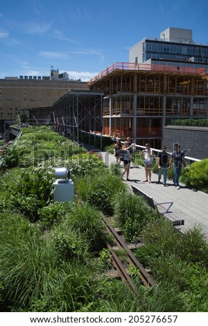 New York, USA - June 20, 2014: Tourists walk in the High Line Park in New York City. The High Line park was created atop an abandoned freight rail line.
