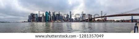 New York / USA - 06-03-2016: Panorama photo of the Brooklyn Bridge and Manhattan with the tops of the skyscrapers reaching the clouds in New York, United States #1281357049