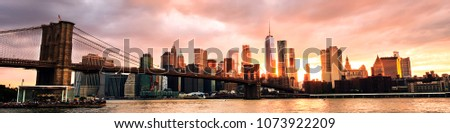 New York, USA. View of Manhattan bridge and Manhattan in New York, USA at sunset. Colorful cloudy sky with skyscrapers. Sun setting behind the skyscrapers