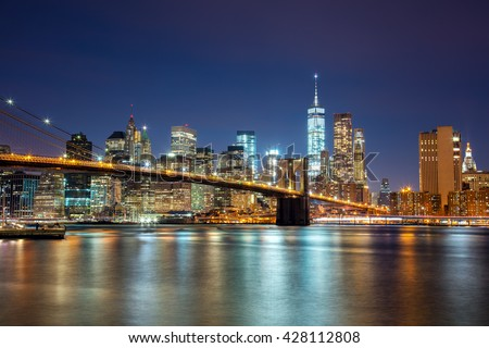New York -  view of Manhattan Skyline with skyscrapers  and famous Brooklyn Bridge by night and city illumination, USA #428112808
