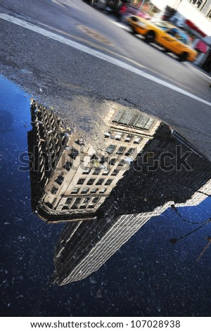 New York Yellow cab pass over a reflection of the Empire State Building in Manhattan, New York.
