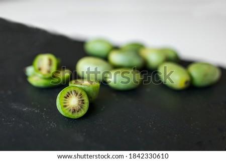 New Zealand exotic food. Berry nergi, or small kiwi. Grey stone background. Baby kiwi or mini kiwi fruits on stone background. Closeup view Photo stock ©
