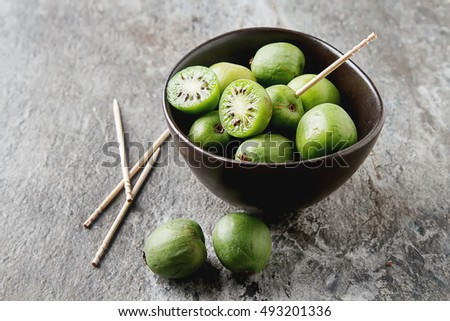 New Zealand exotic food. Berry nergi, or small kiwi. In a brown plate. Grey stone background Photo stock ©