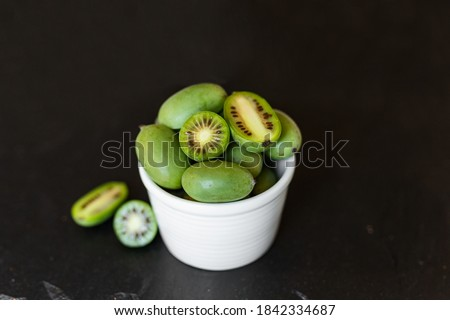 New Zealand exotic food. Berry nergi, or small kiwi. In a white plate. Grey stone background. Baby kiwi or mini kiwi fruits on stone background. Closeup view Photo stock ©