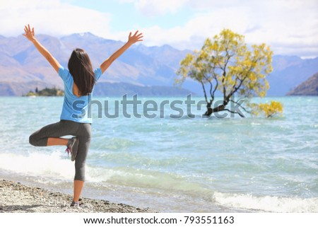 New Zealand morning yoga girl doing tree pose variation doing yoga practice with open arms at Wanaka lake by the lone tree, tourist travel popular attraction in New Zealand. Beach nature landscape.