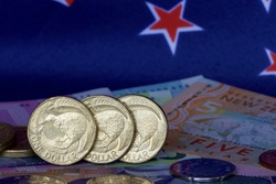 New Zealand one dollar coins with notes and flag.