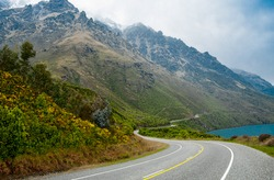 New Zealand Scenic Road:  A two lane road passes beside a lake and winds along the base of a misty mountain south of Queenstown on New Zealand's South Island.