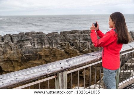 New Zealand travel tourist girl taking smartphone pictures with phone app at Punakaiki Pancake Rocks. Woman in Paparoa National Park, West Coast, South Island, New Zealand