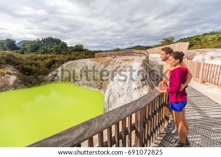 New Zealand travel tourists looking at yellow pond. Tourist couple enjoying famous attraction on North Island, geothermal pools at Waiotapu, Rotorua.