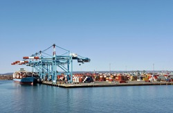 Newark, NJ / USA - View of the container terminal with berthed ship, gantry cranes are loading and discharging cargo from the vessel.