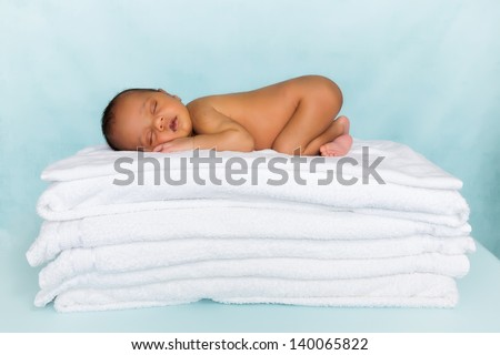 Newborn african baby of 11 days old sleeping on a stack of towels