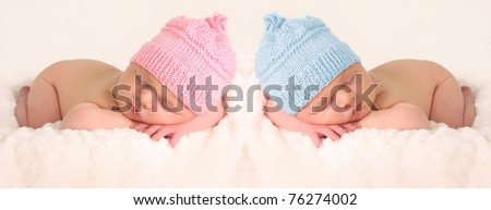 Newborn babies in pink and blue knitted hats.