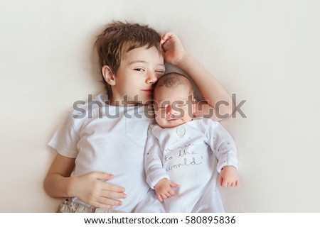 Newborn baby and his older brother lying on a blanket