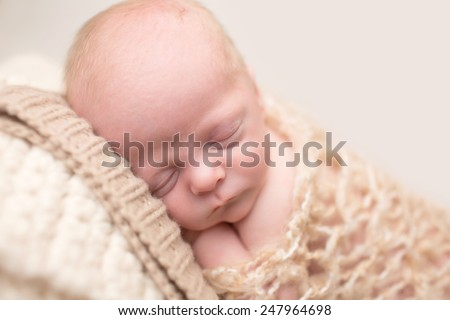 Newborn Baby Asleep, sleeping and taking a nap on a textured blanket posed and curled up