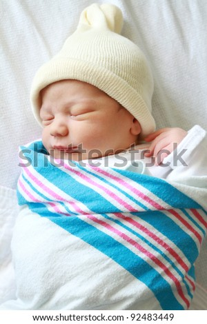Newborn baby asleep, swaddled in hospital blanket and wearing a hat