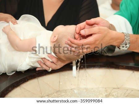 Photo of  Newborn baby baptism by water with hands of priest