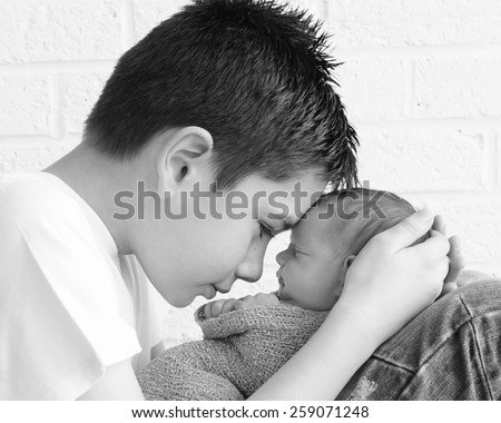 Newborn baby being held tenderly by big brother