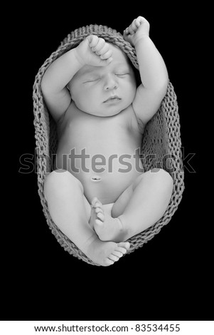 Newborn baby boy asleep wrapped in a knitted cocoon.