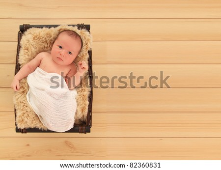 Newborn baby boy awake in a basket. - stock photo