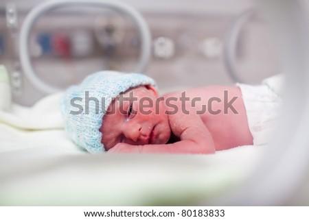 Newborn baby boy covered in vernix in incubator