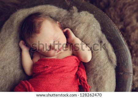 Newborn baby boy in a bowl