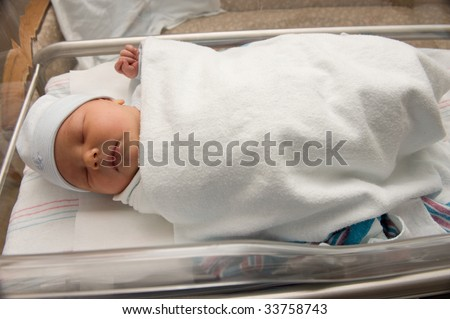 Newborn baby boy in hospital bassinet