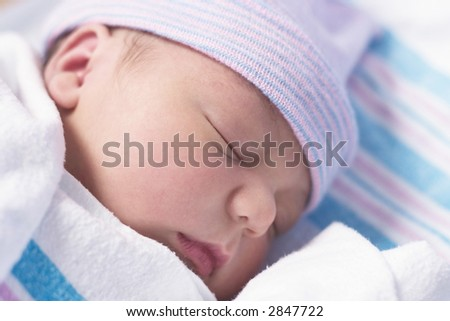 Newborn baby boy in hospital nursery resting peacefully
