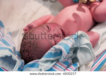 Newborn baby boy resting after being examined in delivery room