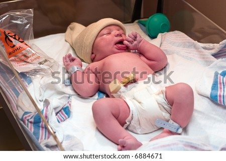 Newborn baby boy resting in hospital post-delivery room