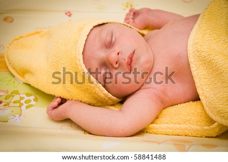 Newborn baby boy sleeping after bath covered by yellow towel