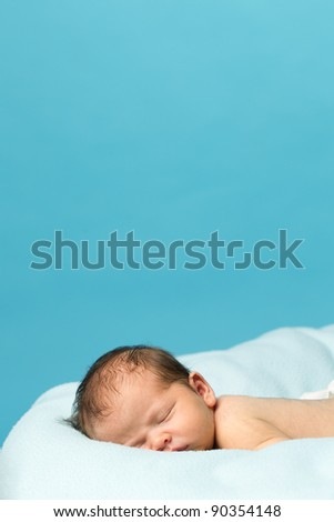Newborn Baby boy sleeping on a blue blanket.